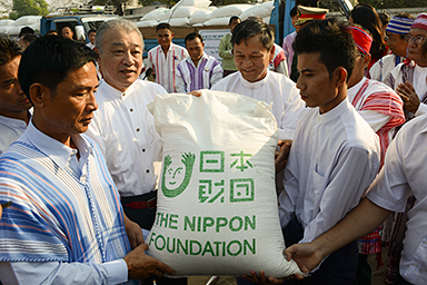 Photo of The Nippon Foundation Chairman Yohei Sasakawa delivering rice to grateful representatives of an ethnic group in Myanmar