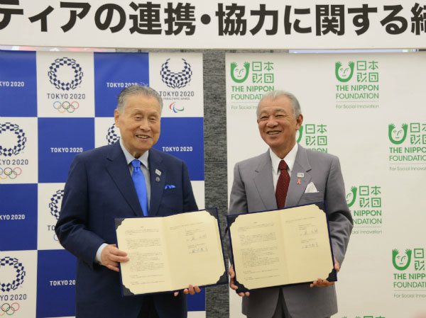 Photo of Tokyo 2020 President Yoshiro Mori (left) and The Nippon Foundation Chairman Yohei Sasakawa (right) with the signed agreements for volunteer partnership