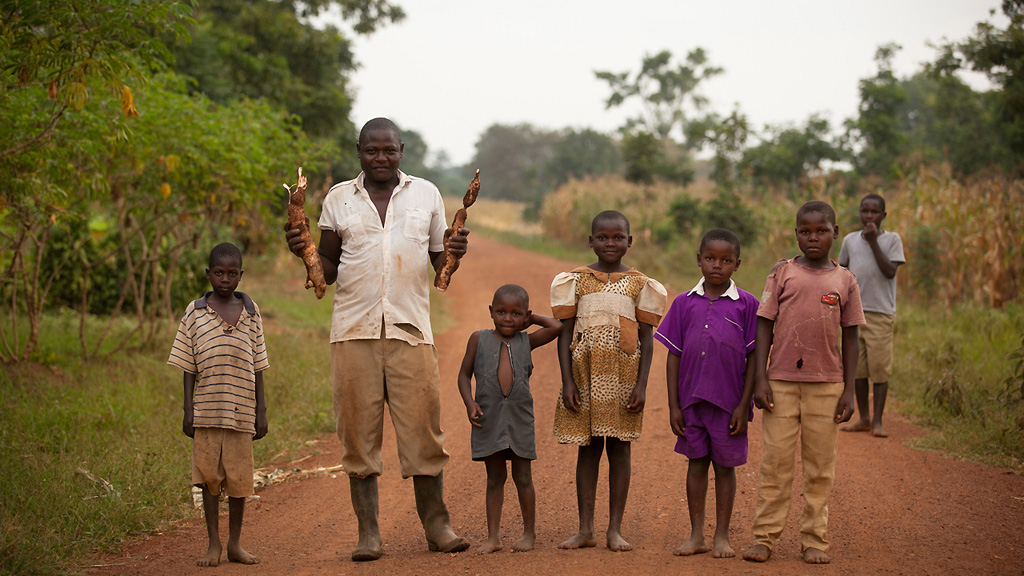 Photo of a smallholder farmer with children in rural Africa, holding a harvested cassava